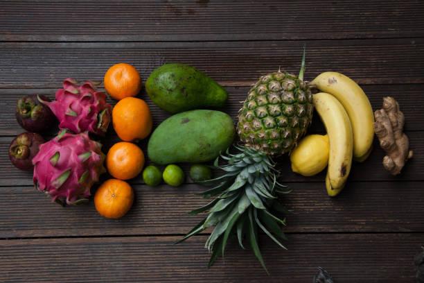 obst-anordnung der verschiedenen lokalen produzieren gegenstände in bali für smoothies einschließlich ingwer, bananen, ananas, mango, limetten, avocado, ananas, ingwer - buddhist tattoos stock-fotos und bilder