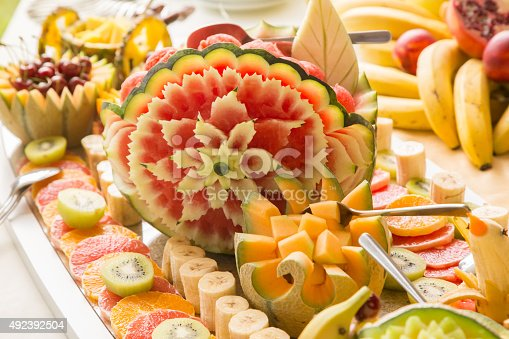 Fresh sliced multi-colored fruit carvings on buffet table.