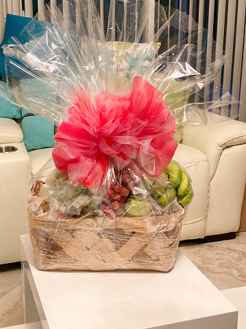 Wrapped fruit basket with a big red bow given as a gift is sitting on a cocktail table in a home.