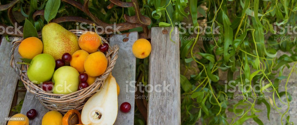 fruit basket is on the bench, it is composed of pear, apples,...