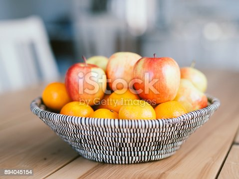 A woven fruit basket sitting on a wood table inside a home.