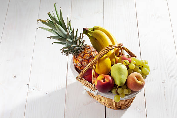 Fruit basket with pineapple, bananas, lemon, apple, peaches, grapes stock photo