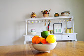 Fruit Bowl on Wooden Kitchen Table; Sideboard in Background
