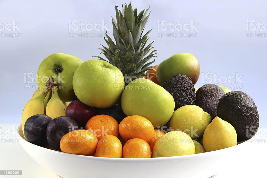 Fruit bowl, with pineapple, apples, bananas, satsumas, oranges, lemons, avocados stock photo