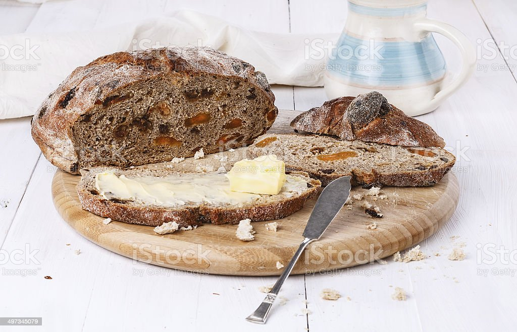 Fruit bread with butter on white wooden background stock photo