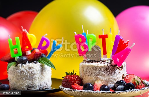 Fruit cake with Happy Birthday written with candles against balloons background