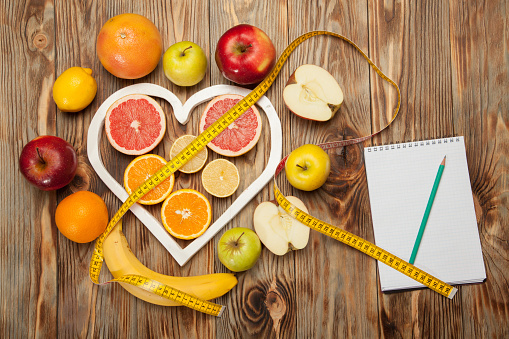 istock Fruit Diet, centimeter and plan on a wooden background 637385718