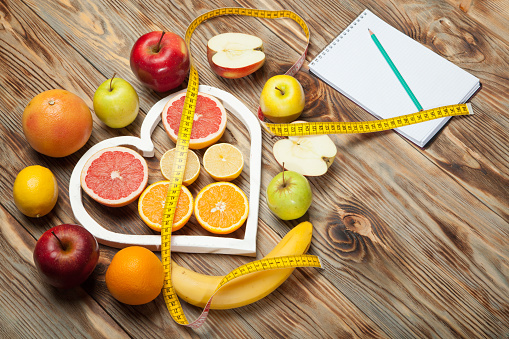istock Fruit Diet, centimeter and plan on a wooden background 638849980
