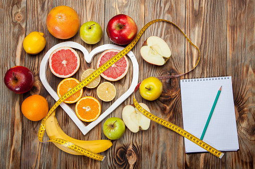 istock Fruit Diet, centimeter and plan on a wooden background 639964310