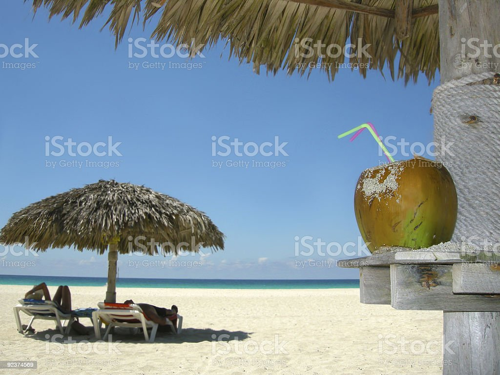 Fruit drink on scenic tropical beach with a palm umbrella royalty-free stock photo