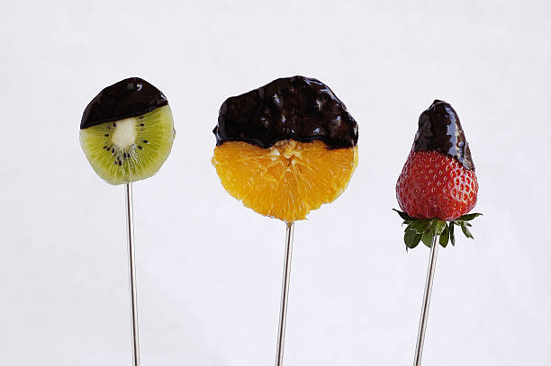 Fruit fondue Fruits dipped in chocolat fondue.Punched fruits chocolate fondue stock pictures, royalty-free photos & images