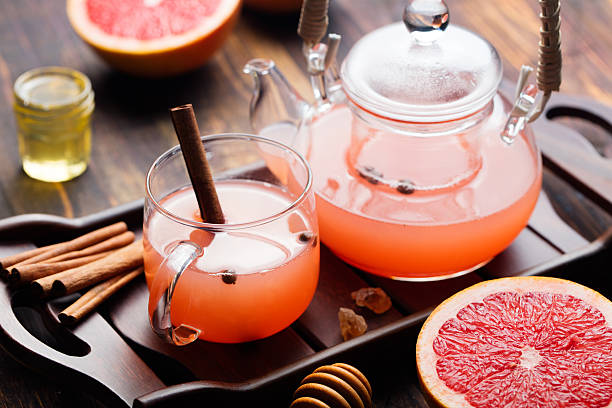 fruits et une infusion d'épices et de miel dans la théière en verre - infusion pamplemousse photos et images de collection