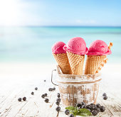 Fruit ice cream with blur beach as background. Served on wooden planks