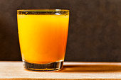 Glass of freshly pressed orange juice on wooden table. copy space