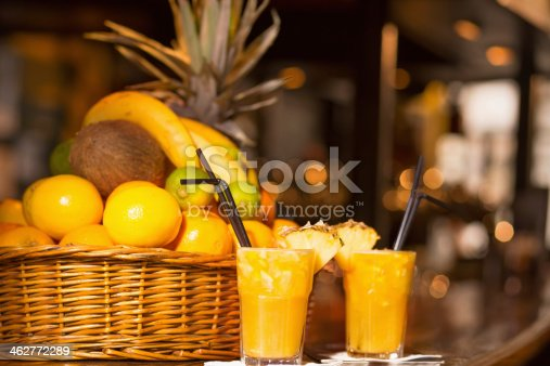 Glasses of fruity cocktail. Fresh mixed fruit juice ready to drink and woven basket full of different fruit. Selective focus. Very shallow depth of field for soft background.