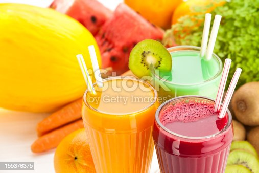 Close Up of Three Glasses of Fruit Juices on White Garden Table. High Angle View.