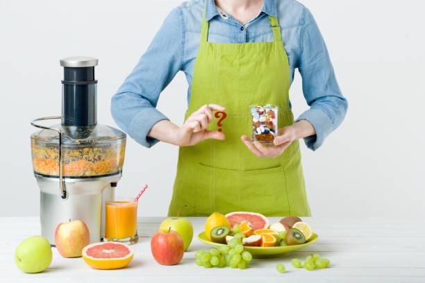 fruit juice, pills and vitamin supplements, woman making a choice - hack rezepte stock-fotos und bilder