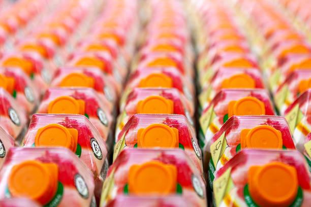 Jus de fruits sur les tablettes des magasins dans le supermarché. Boîtes en carton coloré avec bouchon à vis en plastique. Texture de jus. Délicieuse boisson rafraîchissante. Vue de dessus. - Photo