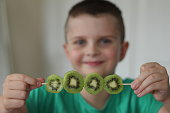 Close up shot with focus on this kiwi fruit kebab. Then in the background out of focus is a young boy age 8 years wearing his green top.