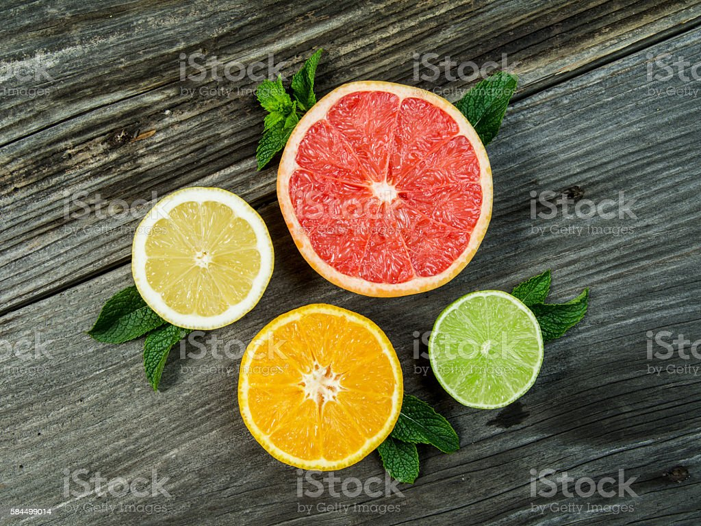 Fruit on an old wood background Photo of a sliced grapefruit, orange, lemon, and lime on a old rustic slab of barn board. Above Stock Photo
