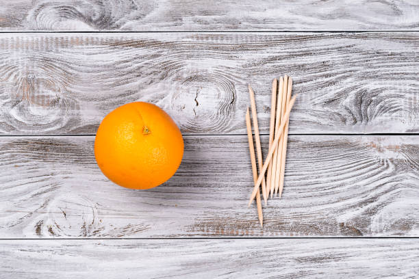 Fruit Orange and orange Wood Sticks Cuticle Pushers for Manicure. Copyspace for your text, banner stock photo
