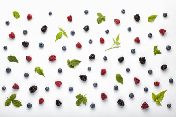 Fruit pattern made of fresh berries and green leaves on white background. stock photo