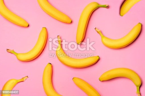 Colorful fruit pattern with bananas over a pink background. Top view.