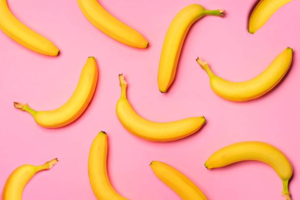 Fruit pattern of bananas over a pink background Colorful fruit pattern with bananas over a pink background. Top view. banana stock pictures, royalty-free photos & images