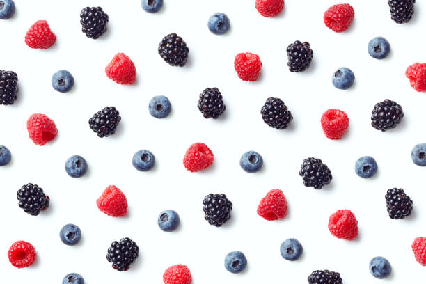 Fruit pattern of colorful wild berries Fruit pattern of colorful wild berries isolated on white background. Raspberries, blueberries and blackberries. Top view. Flat lay berry stock pictures, royalty-free photos & images