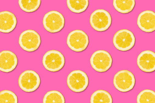 Colorful fruit pattern. Lemon slices on a pastel pink background. Top view.