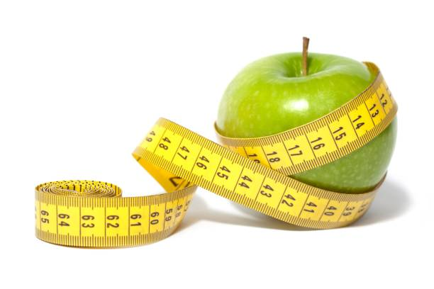 Fruit. A Green Apple and a Measuring Tape tape measure stock pictures, royalty-free photos & images