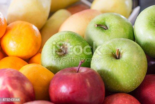 Apples, mandarines, pears stacked in market.