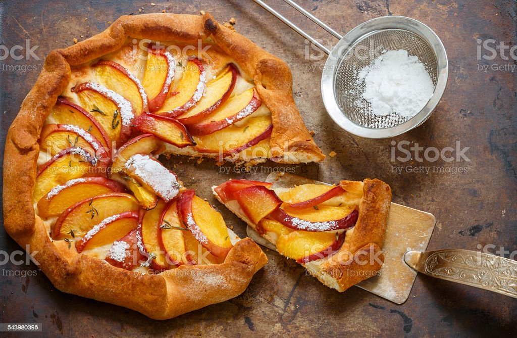 Fruit pie with peaches, nectarines, cinnamon and thyme. Summer dessert stock photo