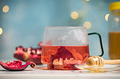 Cup of Pomegranate fruit organic tea with honey in a teacup on a table