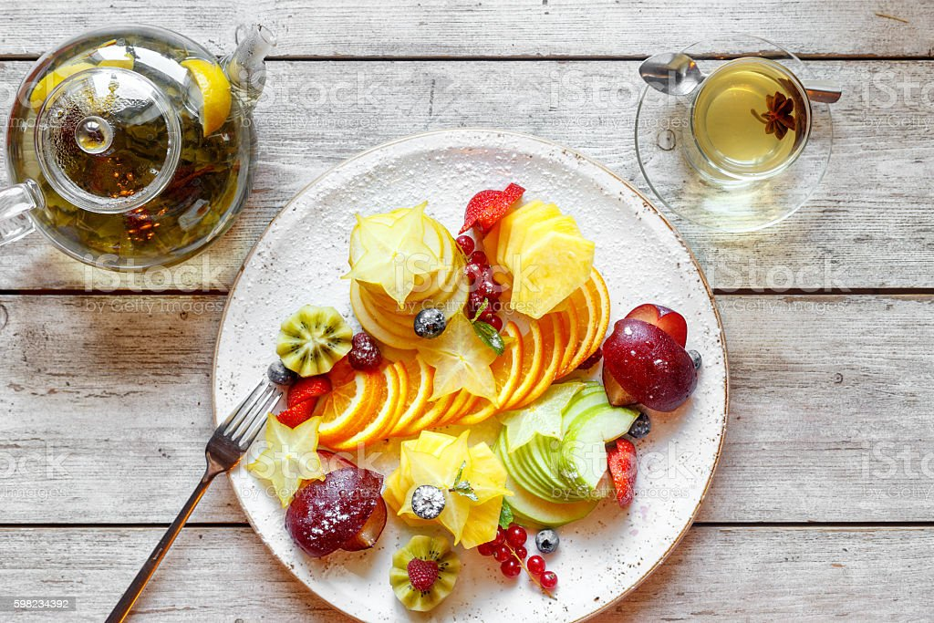 fruit salad and tea on a wooden table foto royalty-free