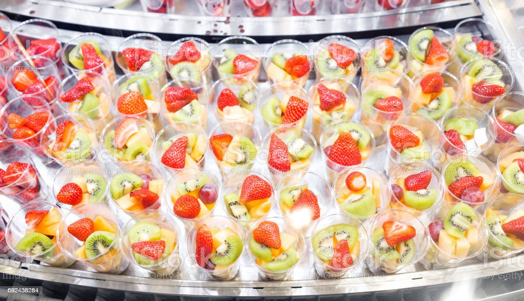 Fruit Salad Arranged In Plastic Cups For Sale. Refrigerator Showcase Or  Buffet. Used In
