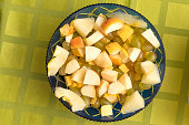 view from above on a table, fruit salad in a salad bowl on a tablecloth background, diet, healthy food, vitamins