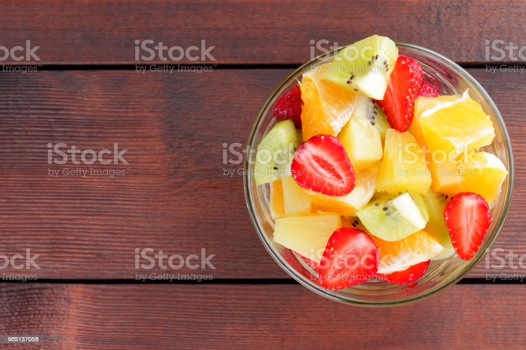 Fruit salad from pineapple, kiwi, orange, strawberry. Multicolored sliced fruit in a transparent dish. Vegetarian food on a wooden background. Citrus fruits for Asian cuisine zbiór zdjęć royalty-free