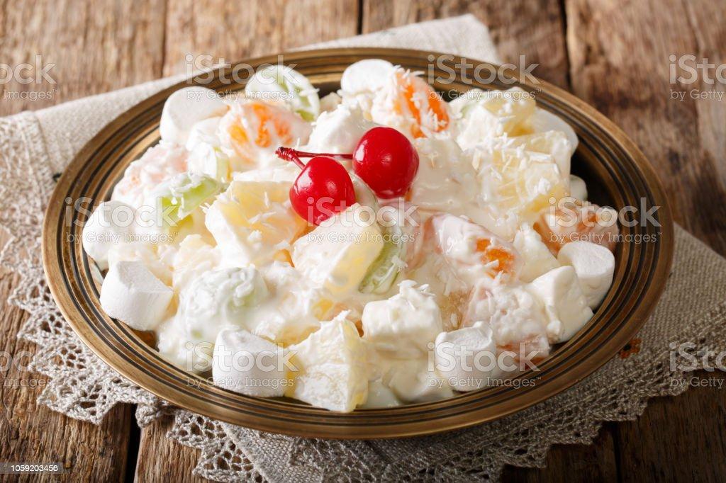 Obstsalat aus Ananas, Orangen, Weintrauben und Kokos mit Marshmallow und Vanille-Joghurt-Nahaufnahme. horizontale – Foto