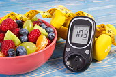 istock Fruit salad, glucose meter, centimeter and dumbbells, diabetes, healthy lifestyle and nutrition concept 983886708