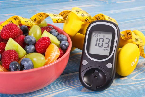 Obstsalat, Blutzuckermessgerät, Zentimeter und Hanteln, Diabetes, gesunde Lebensweise und Ernährungskonzept – Foto