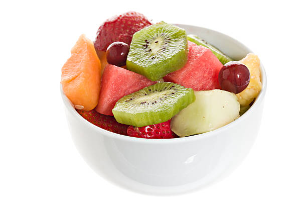 Fruit Salad In A Bowl A close up overhead view of a colorful fruit salad in a white bowl. Isolated on white. fruit salad stock pictures, royalty-free photos & images