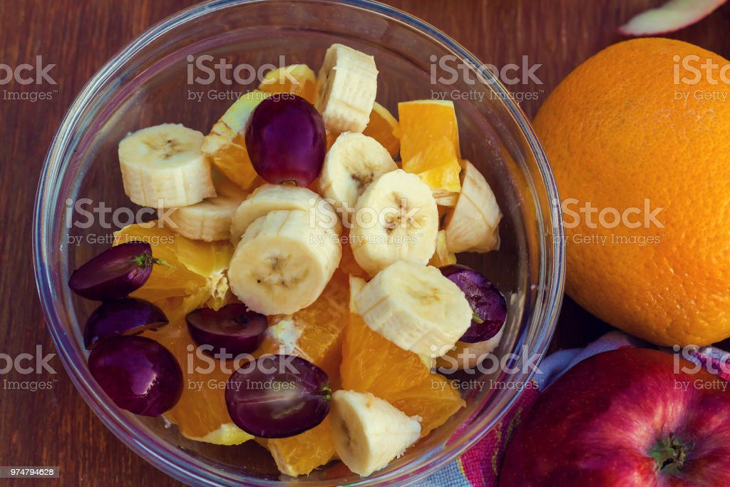 fruit salad of grapes, Apple, banana and orange in salad bowl top view