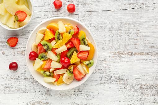 Fruit salad made from chopped strawberries, kiwi, banana, orange and cherry.