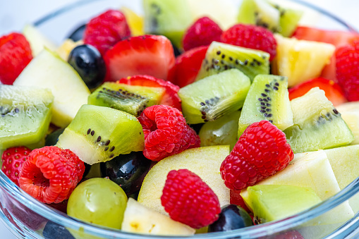 Fruit salad made from various ingredients. Raspberries, strawberries, slices of kiwi, pieces of pear and grapes. Source of vitamins, healthy lifestyle concept.