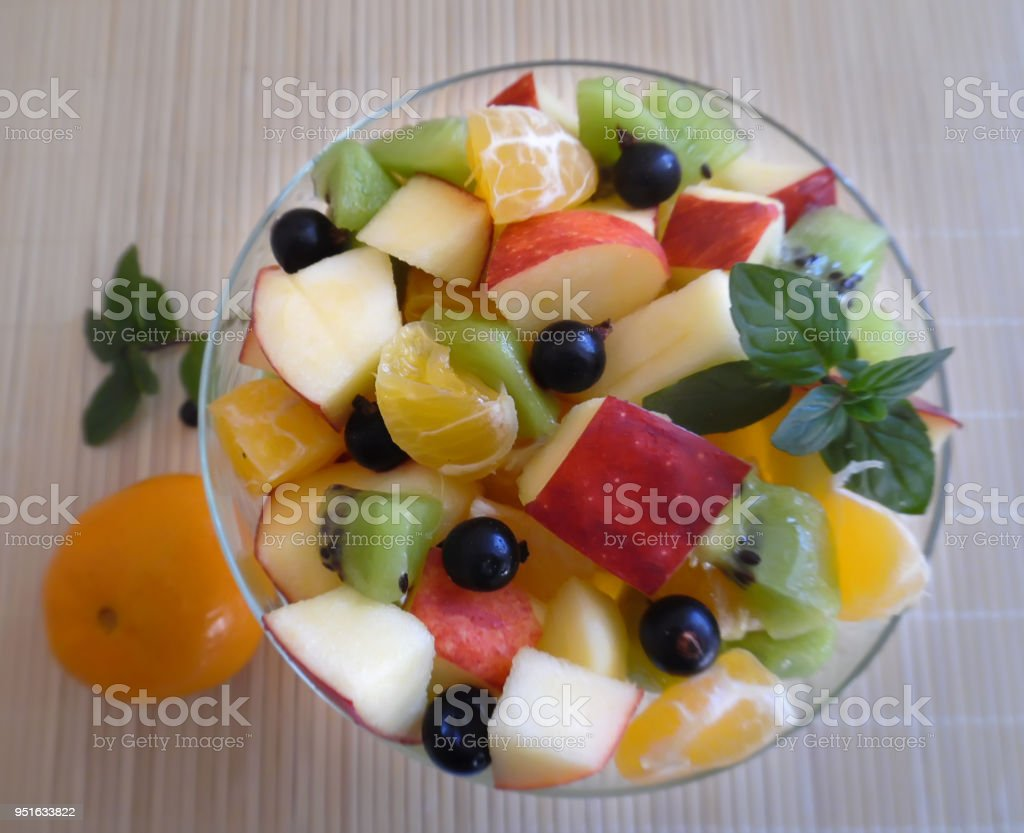 fruit salad on a light background orange kiwi apple mandarin