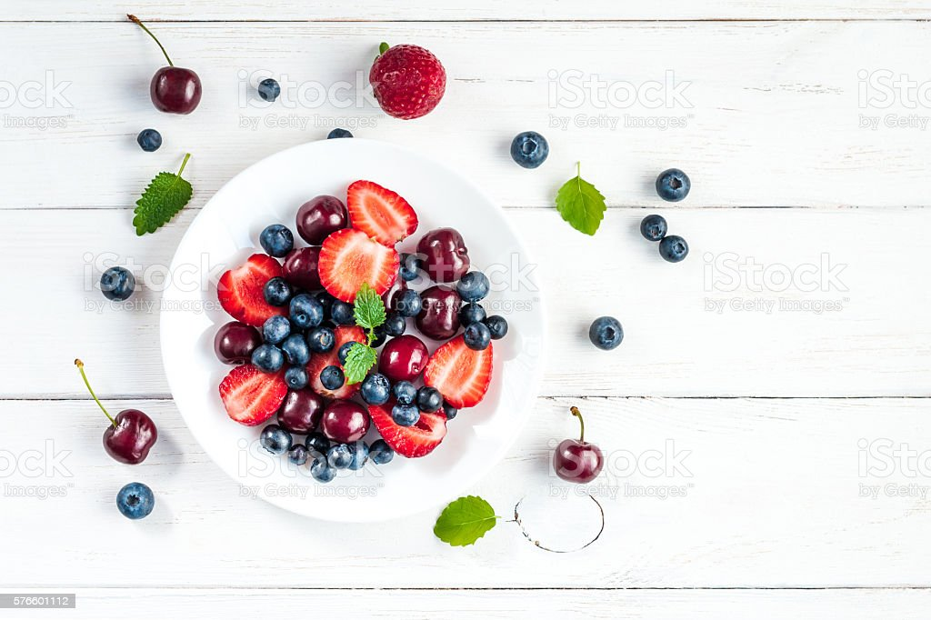 fruit salad on white wooden background, top view, flat lay stock photo