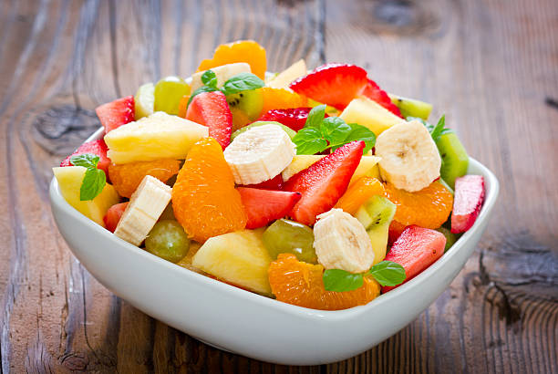 Fruit salad A bowl with fresh, mixed fruit salad on the wooden table fruit salad stock pictures, royalty-free photos & images