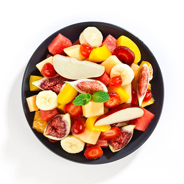 Fruit salad Top view of colorful fruit salad in a gray plate shot on white background. DSRL Studio photo taken with Canon EOS 5D Mark II and EF100mm f/2.8L Macro IS USM Lens fruit salad stock pictures, royalty-free photos & images
