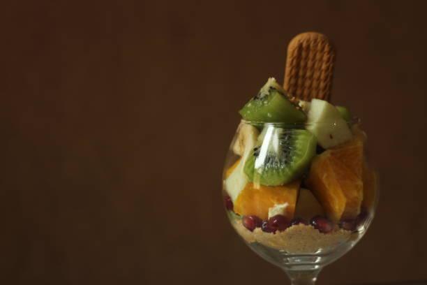 Fruit salad with cookie, studio shot stock photo